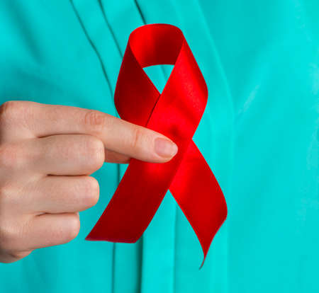 healthcare and medicine concept - female hands holding red AIDS awareness ribbon. Stock Photo