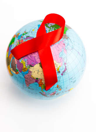closeup a world globe with a red ribbon for the fight against AIDS on a white background. Stock Photo