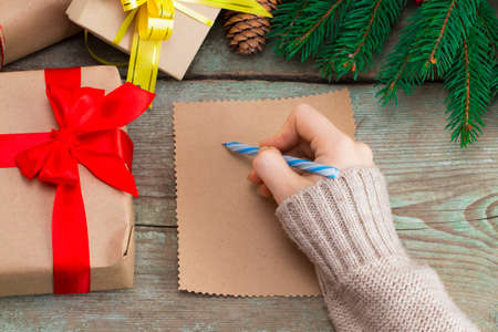 Woman's hand writing a letter on a wooden background with Christmas decorations. Stock Photo