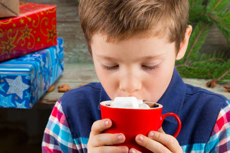 Little boy drinking hot chocolate with marshmallows on the background of gifts, Christmas tree and Christmas decorations.