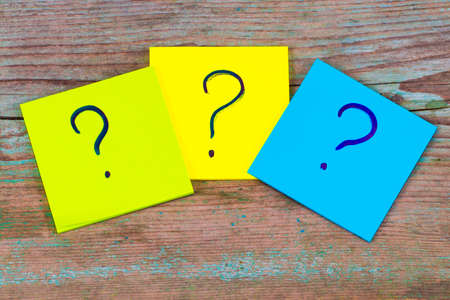questions, decision making or uncertainty concept - a pile of colorful sticky notes with question marks on wooden background. Stock Photo