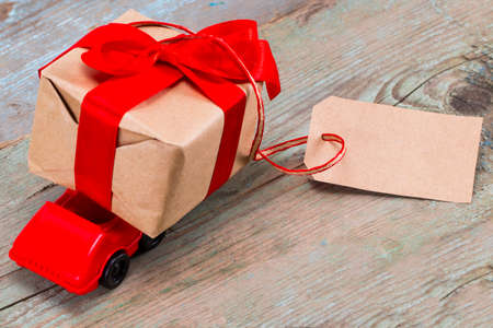 Red toy car delivering gifts box with tag with empty space for a text on wooden background.  Stock Photo