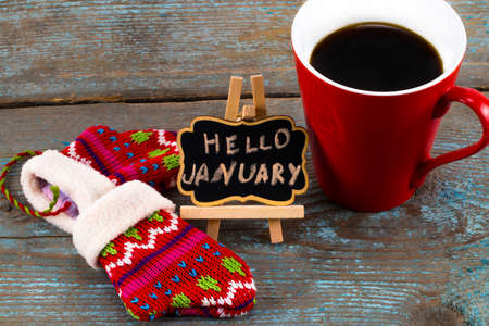 Concept HELLO january message on blackboard with a Cup of coffee and mittens. Standard-Bild