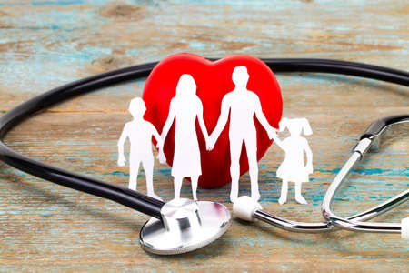 Paper silhouette of family, stethoscope and heart on wooden background. Health insurance concept.