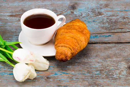 Cup of coffee with bouquet of  tulips and croissant on a wooden background. Valentines, Mothers, Womens Day morning concept. Valentines day breakfast. Top view. Copy space. Stock Photo