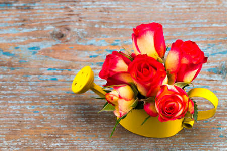 Beautiful flower in watering can on grunge wooden table.With copy space.