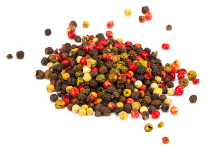 Black, red and white peppercorns isolated on white background. Heap of spice. Mix of different peppers. Stock Photo