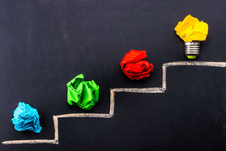 Evolving idea concept with colorful crumpled paper and light bulb on steps drawn on blackboard. Stock Photo - 95713288