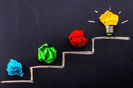 Evolving idea concept with colorful crumpled paper and light bulb on steps drawn on blackboard. Stock Photo - 95523325