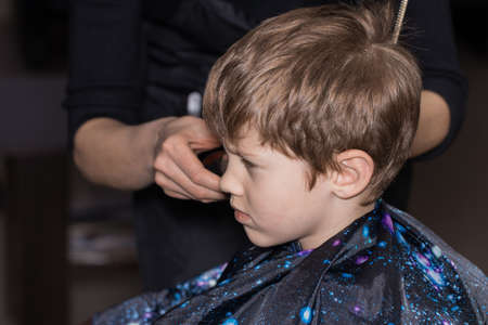 Side view of cute little boy getting haircut by hairdresser at the barbershop. Stock Photo