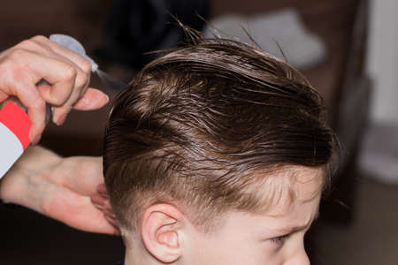 Side view of cute little boy getting haircut by hairdresser at the barbershop using comb and grooming scissors. Closeup.