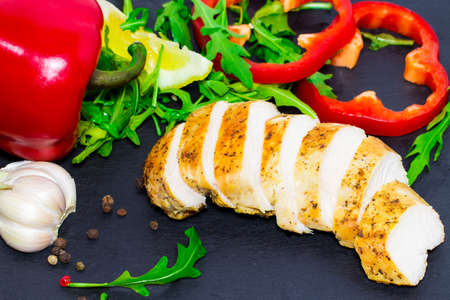 Dietary cuisine - Grilled chicken breast with rucola leaves and vegetables on dark background.