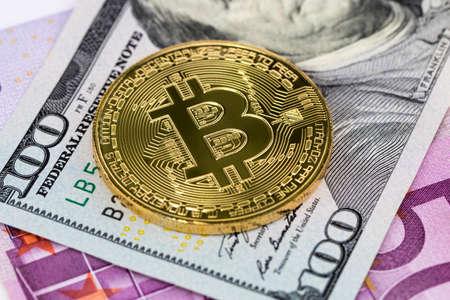 golden bitcoin metallic coin over dollar and euro banknotes.