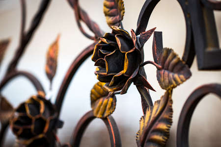 Details, structure and ornaments of forged iron gate. Decorative ornamen with roses, made from metal.