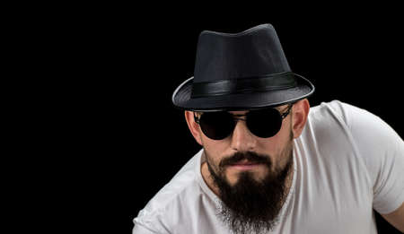 Silhouette of young confident handsome bearded man hipster in hat and sunglasses. Studio shot on dark background Image with free copy space.