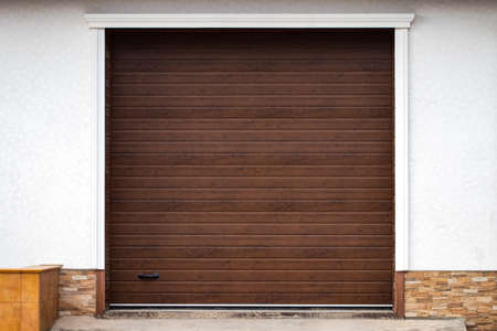 Wooden wall of modern rural garage with the automatic lifted gate. Stock Photo