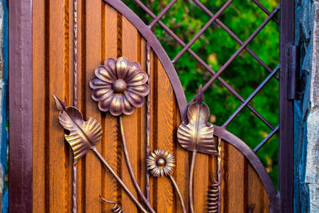 wooden gate with beautiful wrought iron elements flowers. Stock Photo