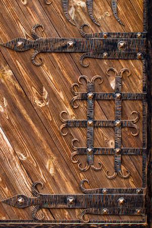 wooden gate with wrought iron elements close up.