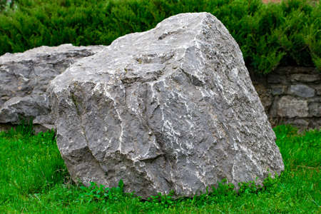 a bunch of ancient stone blocks lying on the grass. Stock Photo