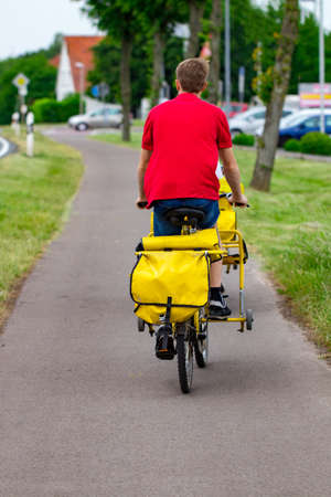 Postman riding his cargo bike carrying out mail in neighborhood.