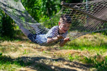 Cheerful  boy lying on hammock in the garden.