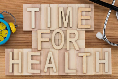time for health -  text in vintage letters on wooden blocks with stethoscope and alarm clock. Medicine concept.