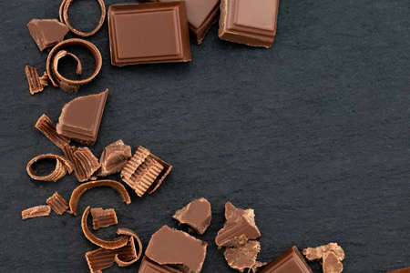 Broken chocolate pieces and chocolate shavings on a dark background. Top view with copyspace for your text. Stockfoto