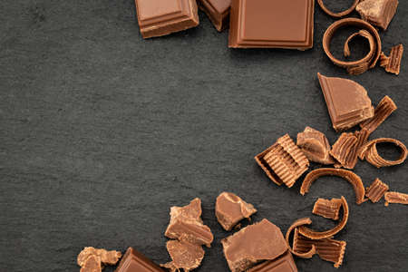 Broken chocolate pieces and chocolate shavings on a dark background. Top view with copyspace for your text. Stock fotó