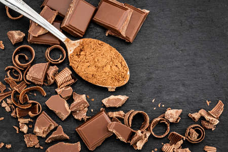 Broken chocolate pieces and cocoa powder on a dark background. Top view with copyspace for your text.