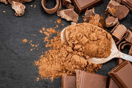 Broken chocolate pieces and cocoa powder on a dark background. Reklamní fotografie - 116372166