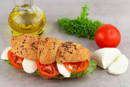 Croissant sandwich with lettuce mozzarella and tomato.