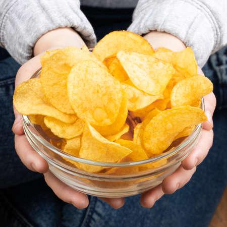 Female hand giving crispy potato chips bowl. Reklamní fotografie