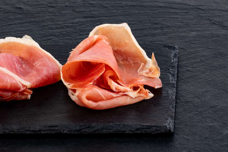Italian prosciutto crudo or spanish jamon and sausages. Raw ham on stone cutting board, copy space, top view.