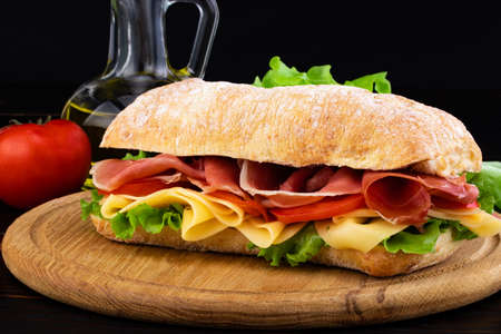 Ciabatta sandwich with lettuce , prosciutto and  cheese on wooden board.