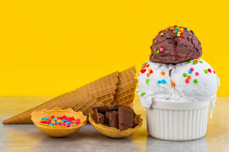 plate of vanilla and chocolate ice cream scoops swith sprinkles chocolate pieces and waffle cones on yellow background.