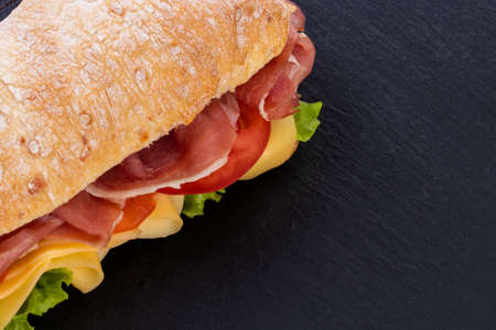 Ciabatta sandwich with lettuce , prosciutto and  cheese over stone background. Top view with copy space. Фото со стока