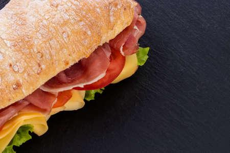 Sandwich ciabatta avec laitue, prosciutto et fromage sur fond de pierre. Vue de dessus avec espace de copie.