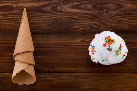 plate of vanilla ice cream scoop swith sprinkles and waffle cones on wooden background with copy space.