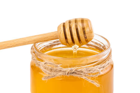Honey pot and dipper isolated on white Stock Photo