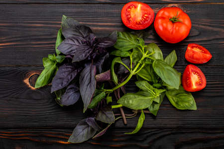 Basil leaves  and tomatoes on wooden