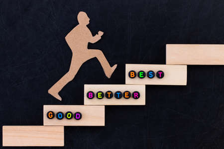 Good - Better - Best paper man climbing the steps to success in a conceptual image over black Stock Photo