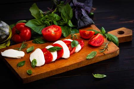 Mozzarella cheese, basil and tomato on slate stone board, copy space. Stock Photo