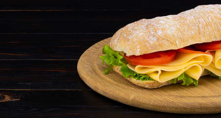 Ciabatta sandwich with lettuce, prosciutto and  cheese on wooden board with copy space.
