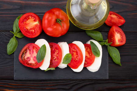 Caprese salad. Mozzarella cheese, tomatoes and basil herb leaves over stone table. Top view. Stock Photo