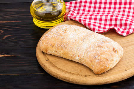 Loaf of ciabatta bread on a cutting board on the dark wooden table. Stock Photo
