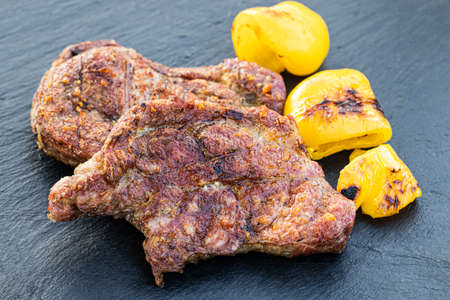 Steaks with grilled vegetables on dark