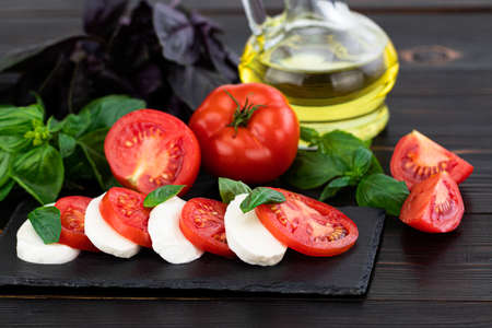 Mozzarella cheese, basil and tomato on slate stone board, copy space. Ingredients for Caprese salad.