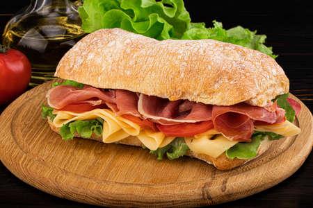Ciabatta sandwich with lettuce , prosciutto and  cheese on wooden board.