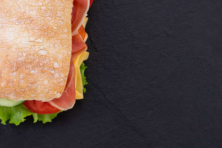Ciabatta sandwich with lettuce, prosciutto and  cheese over stone