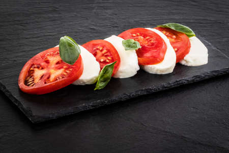 Caprese salad. Mozzarella cheese, tomatoes and basil herb leaves over stone table.